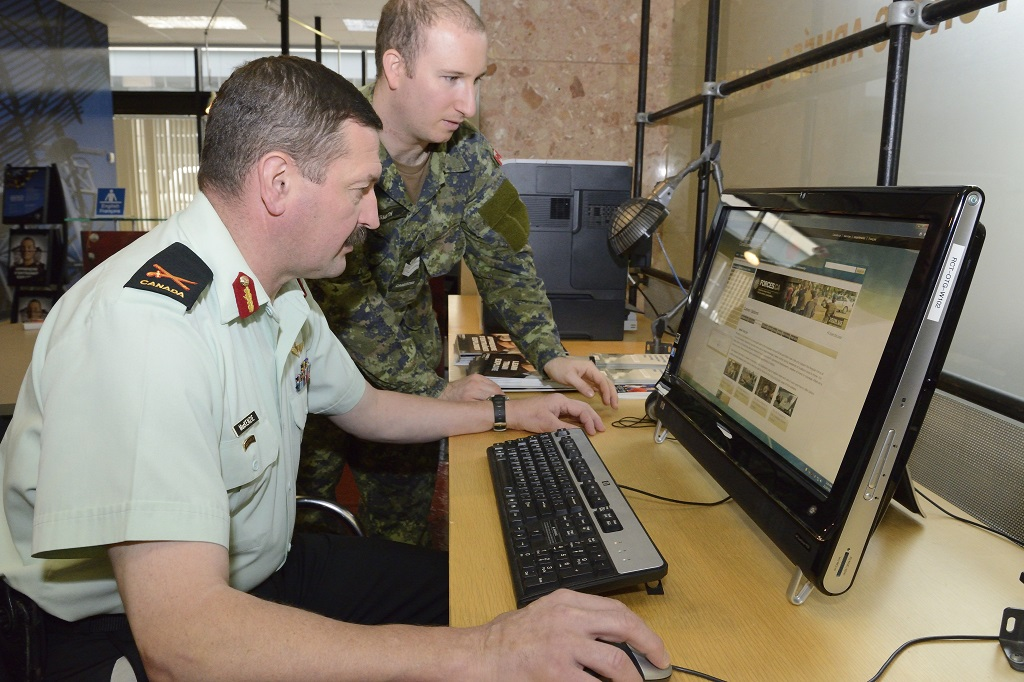 At the Ottawa Recruitment Centre in downtown Ottawa on October 20, 2015, Brigadier-General Rob Roy MacKenzie, Director General Army Reserve and Chief of Staff Army Reserve, speaks with Sergeant Nathan Smith, who recruits full-time for the Cameron Highlanders of Ottawa, Ontario. Photo by: Cpl Dolores Crampton, Directorate of Army Public Affairs. ©2015 DND-MDN Canada.