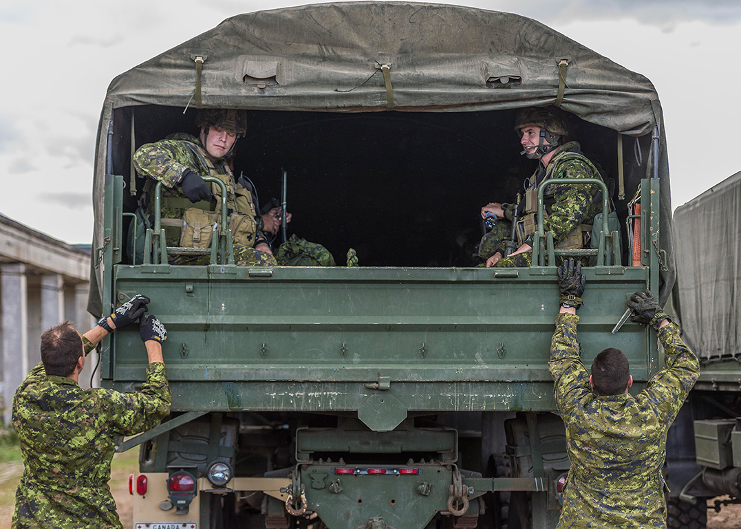 Canadian Armed Forces members board a Heavy Utility Truck Wheeled (HLVW) at Adazi Military Training Area in Kadaga, Latvia in September 2015 during Operation REASSURANCE. The Canadian Army's HLVW fleet is set for replacement by new vehicles with greater cargo capacity and more flexibility. Photo by: Corporal Nathan Moulton, Land Task Force Imagery, OP REASSURANCE. ©DND/MDN 2015.
