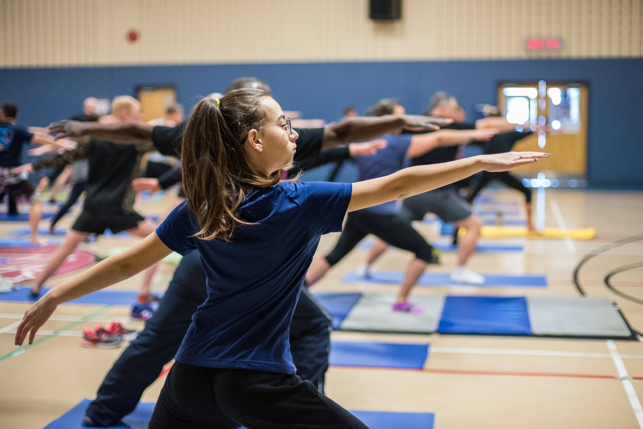 Marie-Lutine Vignal, daughter of Lieutenant Navy Delphine Bonnardot holds the Warrior 2 pose Members of the Defence Team of the 2nd Canadian Division and Joint Task Force (East) participate in Exercise YOGA 2017 (# ExYOGA2017), a yoga session live-streamed from several locations for all – women and men, both civilian and military  – to highlight International Women's Day at Canadian Forces Base/ Area Support Unit Montreal on March 8, 2017. Photo: Corporal Djalma Vuong-De Ramos, 2nd Canadian Division/Joint Task Force (East) ©2017 DND/MDN Canada