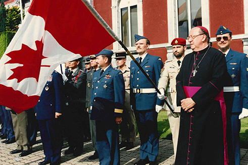 A Canadian soldier holds the Canadian flag during the 45th International Military Pilgrimage in Lourdes, France in 2003.