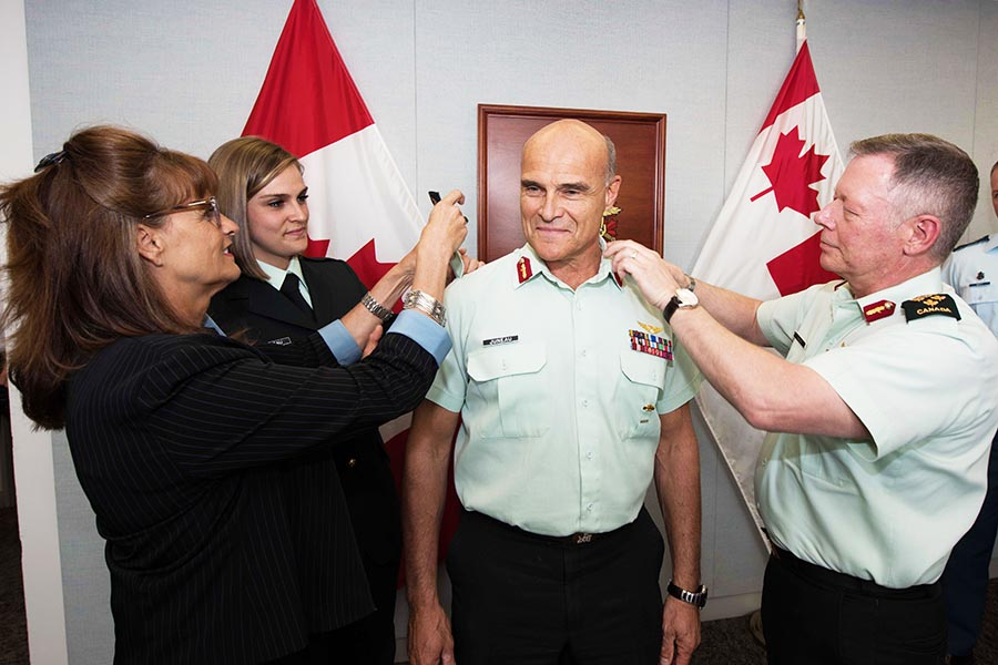Major-General Christian Juneau's wife Andrée Lévesque and daughter Private Alexandra Juneau assist Chief of the Defence Staff General Jonathan Vance in promoting him to the rank of Lieutenant-General at National Defence Headquarters in Ottawa, Ontario, on April 28, 2017. 
