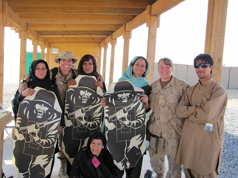 Lieutenant-Colonel Jackie Janzen, second from right, stands with female Afghan National Police candidates and fellow coalition instructors from the United States at Camp Nathan Smith in Afghanistan following training on the 9mm pistol on March 17, 2010. To her left is an interpreter. 