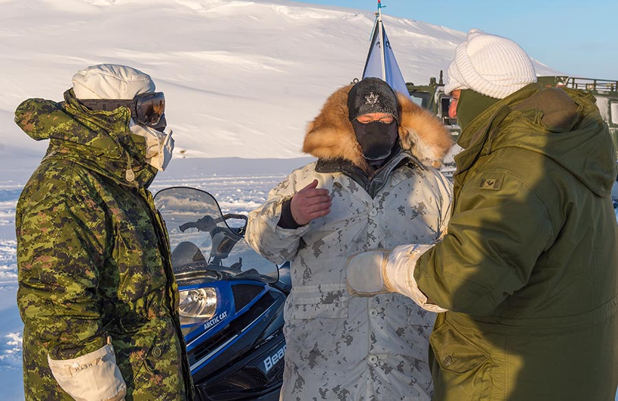 Captain Wayne LeBlanc (centre), Course Commander of the Arctic Operations Advisors course, discusses training procedures with senior trainer Major Gary Johnson and Major-General Simon Hetherington (left), Commander Canadian Army Doctrine and Training Centre. MGen Hetherington visited the Arctic Training Centre on February 24, 2018 in Resolute Bay, Nunavut. Photo: Master Corporal Jennifer Kusche, Canadian Forces Combat Camera. ©2018 DND/MDN Canada.