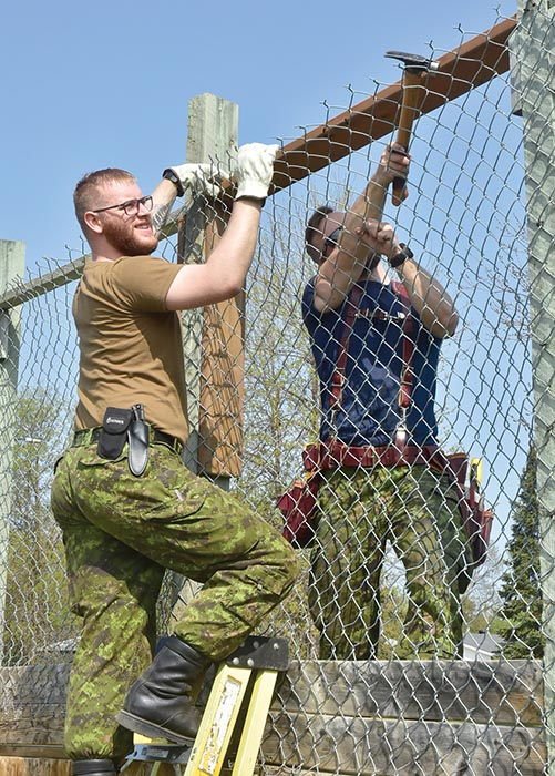 Vehicle technician Private Justin MacDonnel (right) and carpenter Corporal Aaron Legg of Canadian Forces Base Shilo repair a fence at Westridge Community Centre on May 23, 2019 in Brandon, Manitoba during the city's United Way event called Week of Caring. Photo: Jules Xavier, Shilo Stag newspaper.