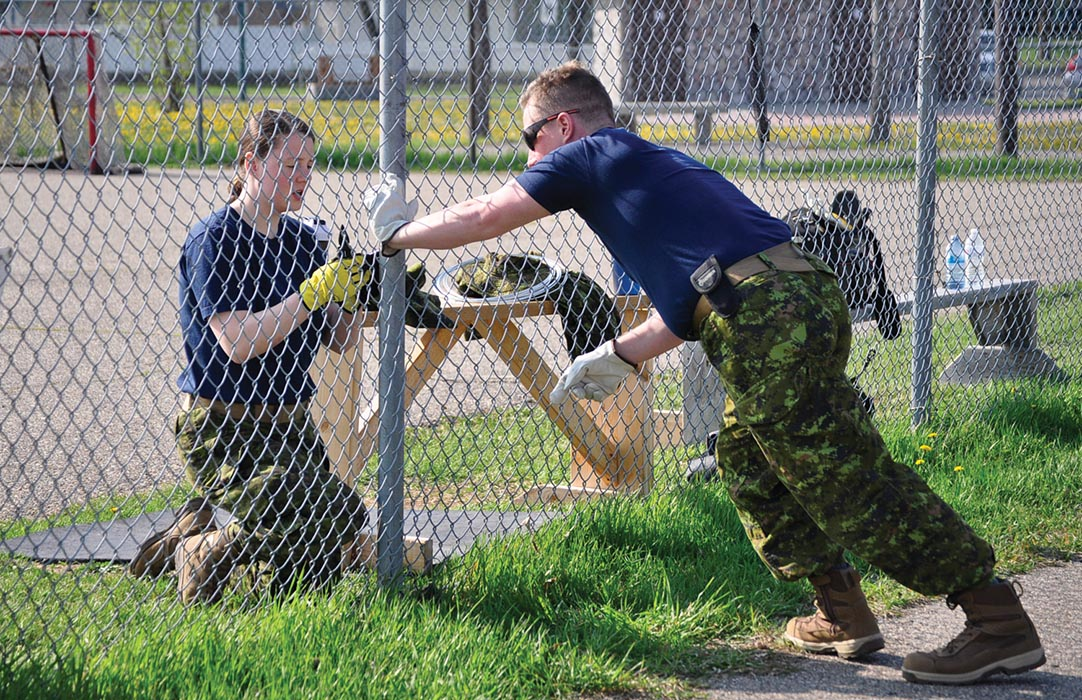 Corporal Didier Loiselle (right), a member of Real Property Operations Unit (West) at Canadian Forces Base Shilo helps repair a chain-link fence at Westridge Community Centre on May 23, 2019 in Brandon, Manitoba during the city's United Way event called Week of Caring. Photo: Jules Xavier, Shilo Stag newspaper.