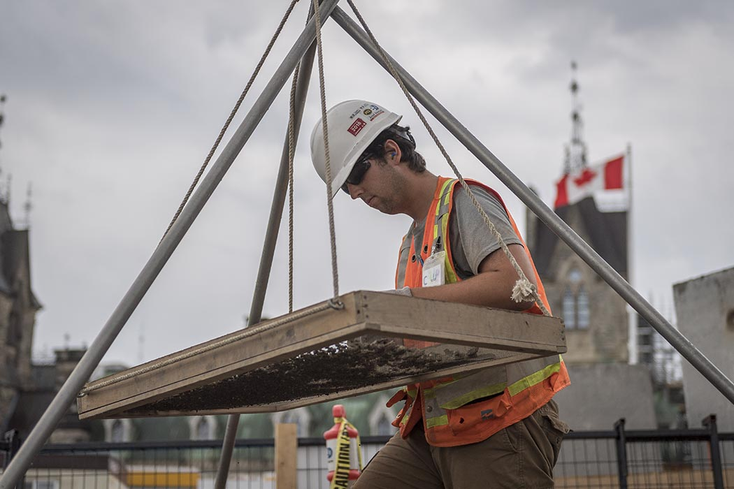 An archeologist from the Centre Block Rehabilitation Project pans for artifacts found in the remains of a 19th-century guard house on Parliament Hill in Ottawa, Ontario on July 30, 2019. Photo: Able Seaman Camden Scott, Army Public Affairs. ©2019 DND/MDN Canada.