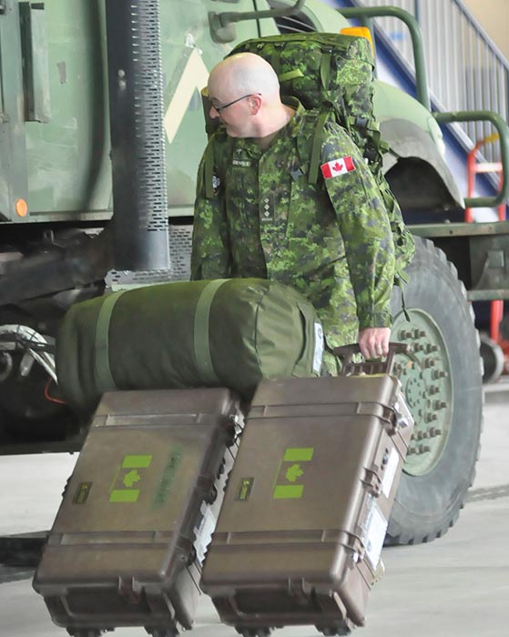 2nd Battalion, Princess Patricia's Canadian Light Infantry Padre Captain Troy Dennis loads a kit bag and battle boxes as the battalion prepares to deploy on Operation REASSURANCE in Latvia on July 8, 2019. Photo: Jules Xavier, Shilo Stag newspaper.