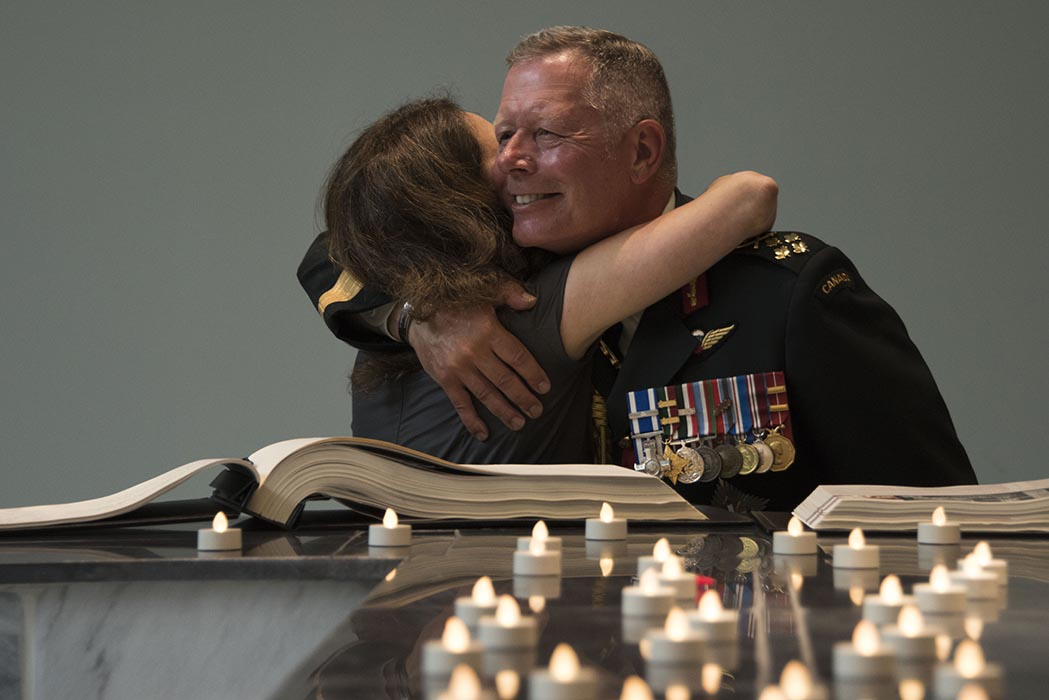 General Jonathan Vance, Chief of the Defence Staff of the Canadian Armed Forces, hugs a fallen soldier's family member following the Kandahar Cenotaph Rededication Ceremony at the Afghanistan Memorial Hall at National Defence Headquarters (Carling) in Ottawa, Ontario, on August 17, 2019. Photo: Ordinary Seaman Alexandra Proulx, Army Public Affairs. ©2019 DND/MDN Canada.