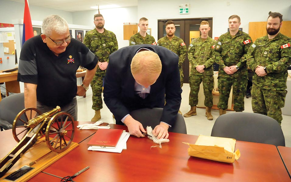 Soldiers from 1 Royal Canadian Horse Artillery and Royal Canadian Artillery Museum board chair Chuck LaRocque look on as Royal Canadian Artillery Museum director Andrew Oakden opens the bubble wrap containing two medals given to Major-General Tom Strange bought at auction for $50,000. Photo: Jules Xavier, Shilo Stag ©2019 DND/MDN Canada.