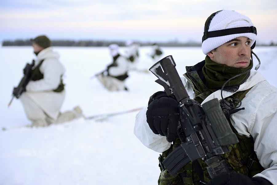 Master Corporal Michel St-Pierre of 3rd Battalion, Royal 22e Régiment, wearing the Canadian Army's Winter Operations camouflage pattern, stands watch with his section during Exercise RAFALE BLANCHE in St Sylvestre, Québec on February 3, 2014. Photo: Master Corporal Patrick Blanchard, Canadian Forces Combat Camera. ©2014 DND/MDN Canada.