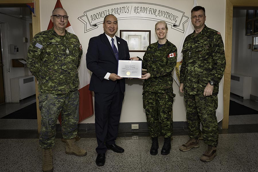 Jon Reyes, presents Corporal Isabelle Thibodeau with a Certificate of Recognition