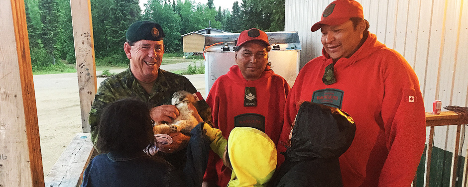 Slide - Warrant Officer Barry Borton, an army instructor, plays with a local puppy while talking to children in Wapekeka with Canadian Ranger Master Corporal Jacob McKay, and Sergeant Spencer Anderson
