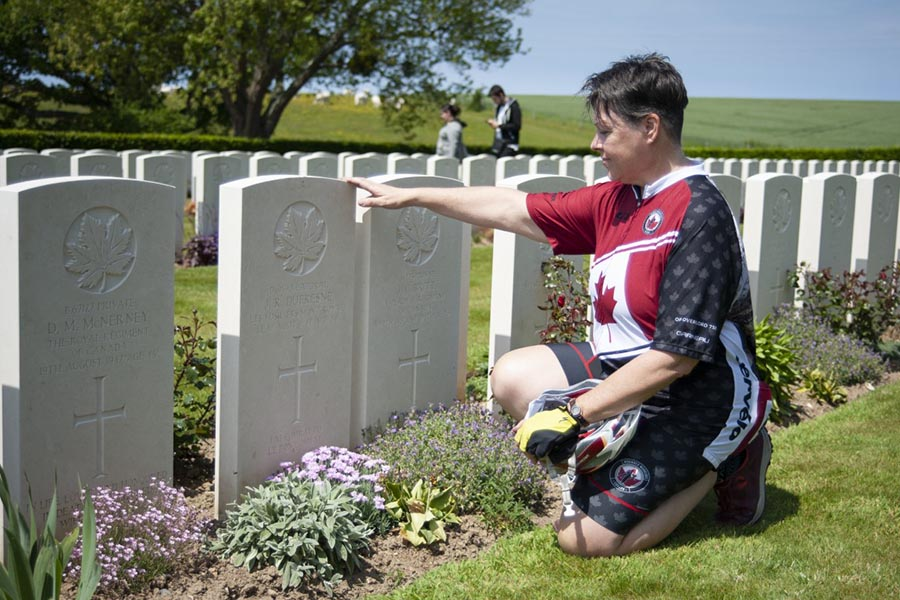 On the first day of Wounded Warriors Canada's Battlefield Bike Ride 2019, rider Kathleen Short, whose spouse is a former military member, kneels at the grave of her great uncle at the Dieppe Canadian War Cemetery. Photo: John's Photography, Sooke, BC