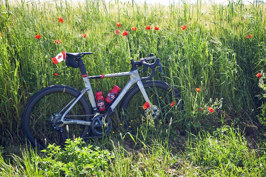 A bike owned by a member of the Wounded Warriors Canada's Battlefield Bike Ride 2019 team with Canadian flag attached rests against a field of poppies outside the city of Deauville, France. Photo: John's Photography, Sooke, BC