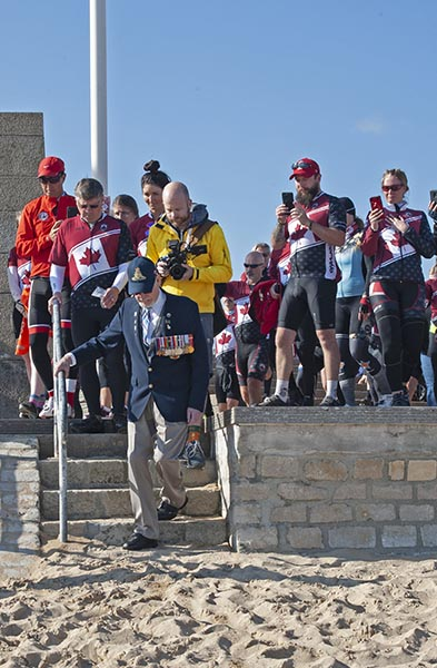 Second World War Veteran Russell Kaye is joined by members of Wounded Warriors Canada's Battlefield Bike Ride 2019 as he sets foot on Juno Beach for the first time in 75 years. He was one of thousands of brave Canadians who stormed the beach as part of the historic D-Day Landings near Courseulles-sur-Mer, France. Photo: John's Photography, Sooke, BC