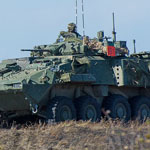 Members of 2nd Battalion, Princess Patricia's Canadian Light Infantry advance on an objective with the support of a Light Armoured Vehicle during a Platoon level group attack with live firing during Exercise KAPYONG MACE at CFB Shilo, Manitoba on September 26, 2015. Photo: MCpl Louis Brunet, Canadian Army Public Affairs